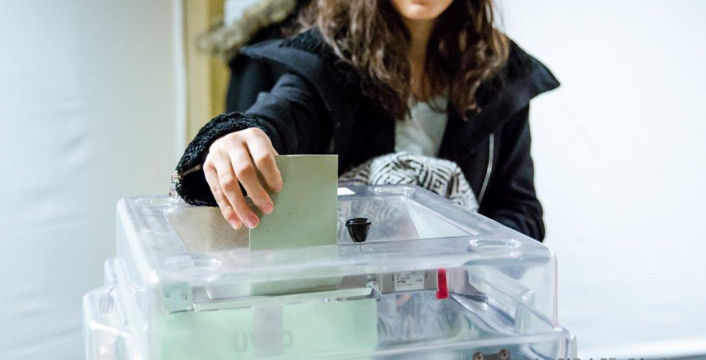 Une personne glisse un bulletin dans l'urne